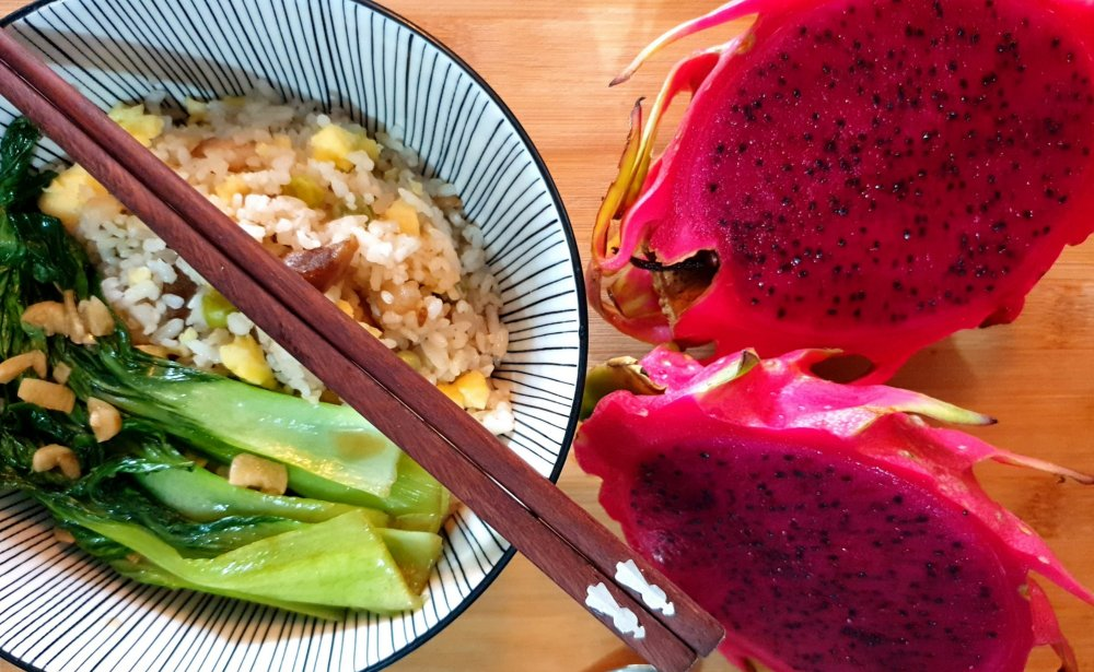 Oriental rice meal with vegetables and dragon fruit on the side